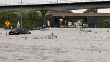 Cars are swept away outside Toombul shopping centre,