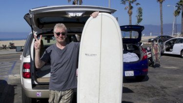 Neil Lawrence with his new surfboard in Santa Monica, Los Angeles.