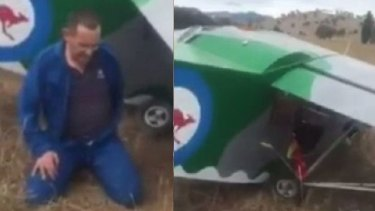 A man sits in shock after crash landing in a paddock, near Tumut.