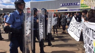 Riot police come face to face with protesters in Kalgoorlie.