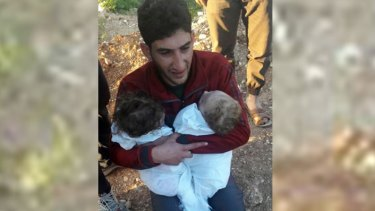 A man holds his twin babies who were killed during the chemical weapons attack in Syria. Trump was said to be impacted by such images.