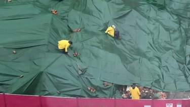 Workers at the Carlton site put tarpaulins over the remains of the pub.