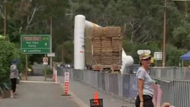 A truck laden with hay drags away the finish line of the Tour Down Under.