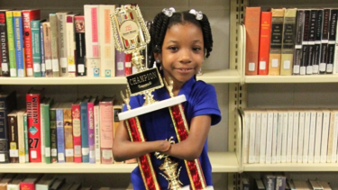 Anaya, 7, cradles her trophy after the handwriting contest.