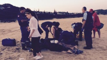 Bodyboarder Dale Carr being treated at the scene after a shark attack at Port Macquarie.