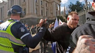 A Victorian police officer appears to give a Reclaim Australia supporter a solidarity handshake at a rally on Sunday.
