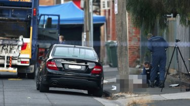 Forensics officers examine the man's body on St Phillip Street.
