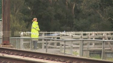 A police officer overlooking the creek at Mooroolbark, near the railway line.