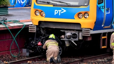 An emergency worker inspects the crushed car at Surrey Hills station.