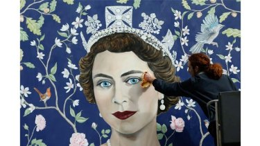 Workmen install a new mural, by Frederick Wimsett, of Queen Elizabeth II to mark her 90th birthday celebrations in central London.