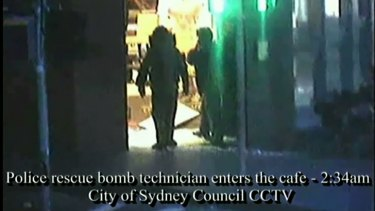 Bomb squad technicians enter the cafe after the siege.