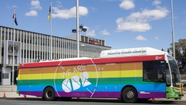 A bus painted in rainbow colours in support of marriage equality parks in front of the ACT Legislative Assembly.