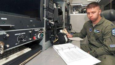US Air Force Captain Cory Kuehn, with the 625th Strategic Operations Squadron, reads his technical order booklet in front of the Airborne Launch Control System procedures trainer on Offutt Air Force Base, Nebraska.