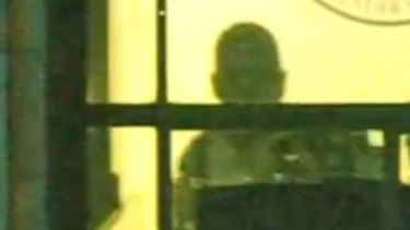 Gunman Man Haron Monis seen through a window of the Lindt cafe.
