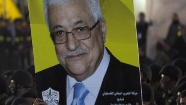 Palestinians hold up a poster showing President Mahmoud Abbas on December 31, as they celebrate the 50th anniversary of the founding of the armed wing of the Fatah movement, al-Asifa, in Ramallah.