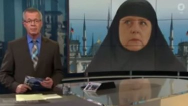 """ARD's anchor hosting <i>Report from Berlin</i> with the """"Muslim Merkel"""" montage in the background."""