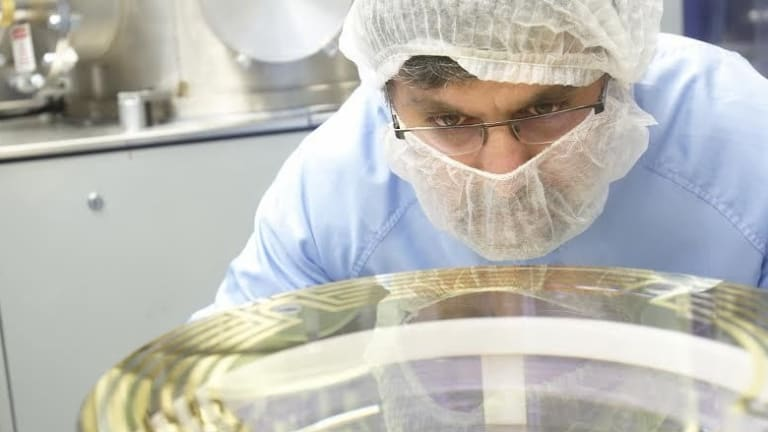 CSIRO technicians work on one of the mirrors to be used in LIGO in the detection of gravitational waves.