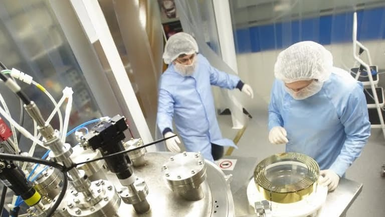 CSIRO technicians working on optical equipment used to detect gravitational waves.