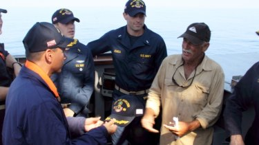 Navy Commander John Barsano welcomes Ron Ingraham aboard USS Paul Hamilton after his rescue on Tuesday.