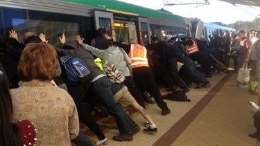 People get off the train to help push the train and free the man.