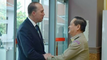 Australian Immigration Minister Peter Dutton and Cambodian Department of Immigration director-general Sok Phal shake hands in Phnom Penh last month.