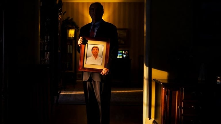 John Hughes holds a portrait of his son Thomas, a Wall Street banker who committed suicide in May.