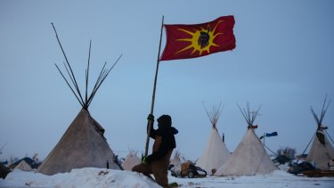 An unidentified man removes a Mohawk Warrior Society flag from his campsite at the Oceti Sakowin camp. The The Mohawk flag came to prominence during the 1990 Canadian Oka Crisis, when the military confronted indigenous people in a major armed conflict for the first time in modern history. .
