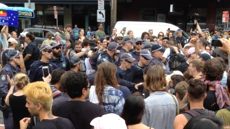 A group of police begins to back away from the crowd of protesters.