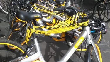The oBikes appear to be wrapped in official City of Melbourne tape declaring them illegal litter.