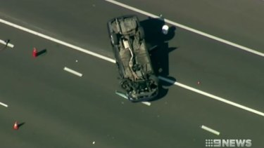 The Holden Commodore flipped and landed on its roof on the freeway.