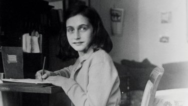 Anne Frank at her desk in her house in Amsterdam.