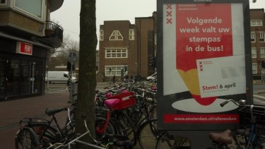"""""""Next week your voting card's coming in the mail! Vote April 6,"""" a sign reads in Amsterdam."""