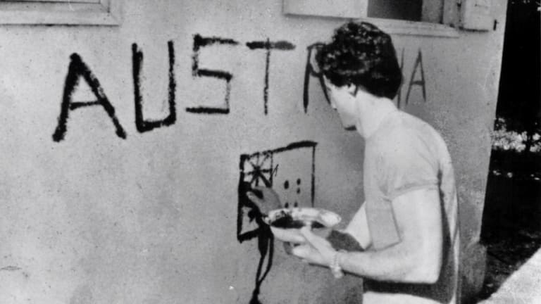 """Greg Shackleton paints """"Australia"""" on a shop wall in Balibo in East Timor in 1975. He and five other journalists were killed while covering Indonesia's invasion."""