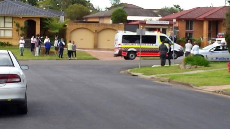Residents gather after a man was arrested for allegedly committing a terrorist act.
