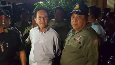 Cambodian Opposition Leader Kem Sohka pictured in cufflinks as he is led away by  government officials.