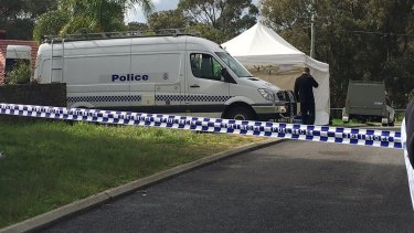 Police forensic officers at the Orelia home where Aaron Pajich's body was found.