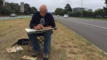 Canberra artist Christopher Oates works on a painting in the middle of six-lane Adelaide Avenue.