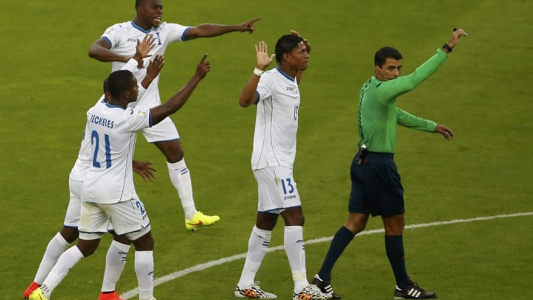 Honduras players protest the disputed goal.