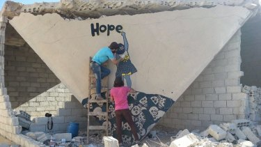 Graffiti artists at work in the ruins of the besieged Syrian city of Daraya.