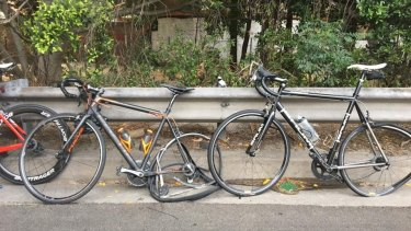 Damaged bikes propped against the road's railings.
