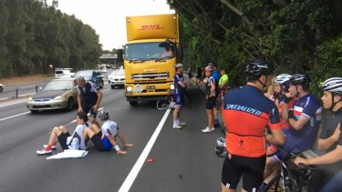 Michael Long (left) sits on the ground, propped up by another rider, before an ambulance arrives.