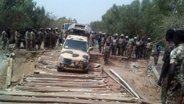Nigerian troops cross the Kaffin-Hausa bridge, which earlier had been destroyed by terrorists and reconstructed by military engineers at Damasak in north-eastern Nigeria Borno State.