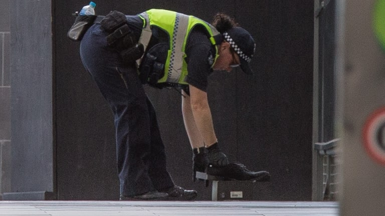 A police officer removes the 'suspicious' shoes.