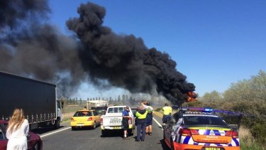 A truck has rolled and caught fire on the Federal Highway.