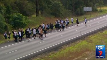 Students walk to safety as their bus burns in the northbound lane of the Bruce Highway near Sippy Downs, north of Brisbane.