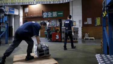 An employee operates a forklift to transport a pallet stacked with bundles of the Apple Daily newspaper, published by Next Media, at the company's printing facility in Hong Kong.