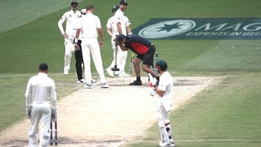 Wake up: A groundsman takes a sledgehammer to the MCG pitch during the Boxing Day Test.