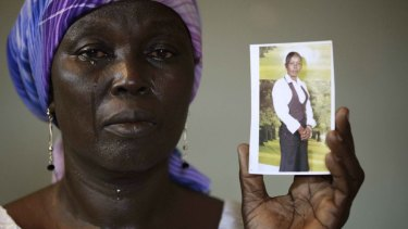 Martha Mark, the mother of kidnapped school girl Monica Mark, cries as she shows her photo in May 2014.