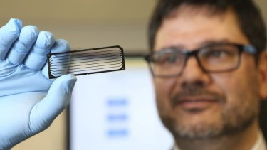 Gene machine: Kinghorn Cancer Centre director David Thomas holds up a flow cell that contains eight human genomes.