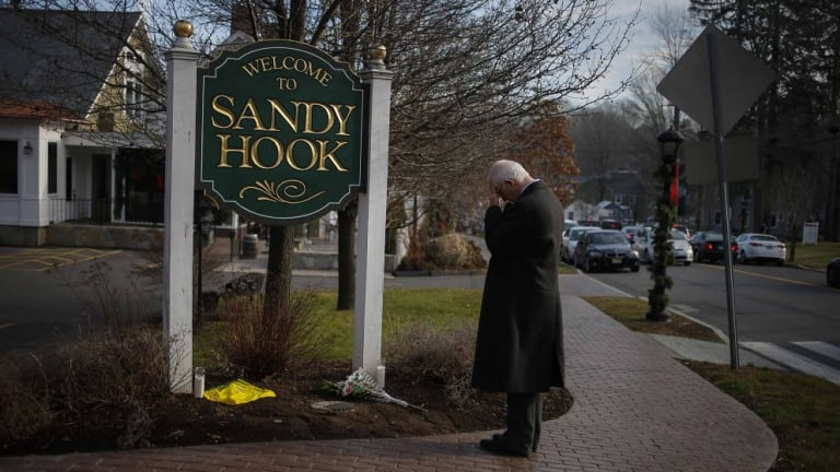 A man pauses to mourn at the entrance to the town of Sandy Hook on December 15, 2012, in the aftermath of the tragedy.